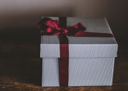 A white gift box with a red ribbon tied in a bow around it.