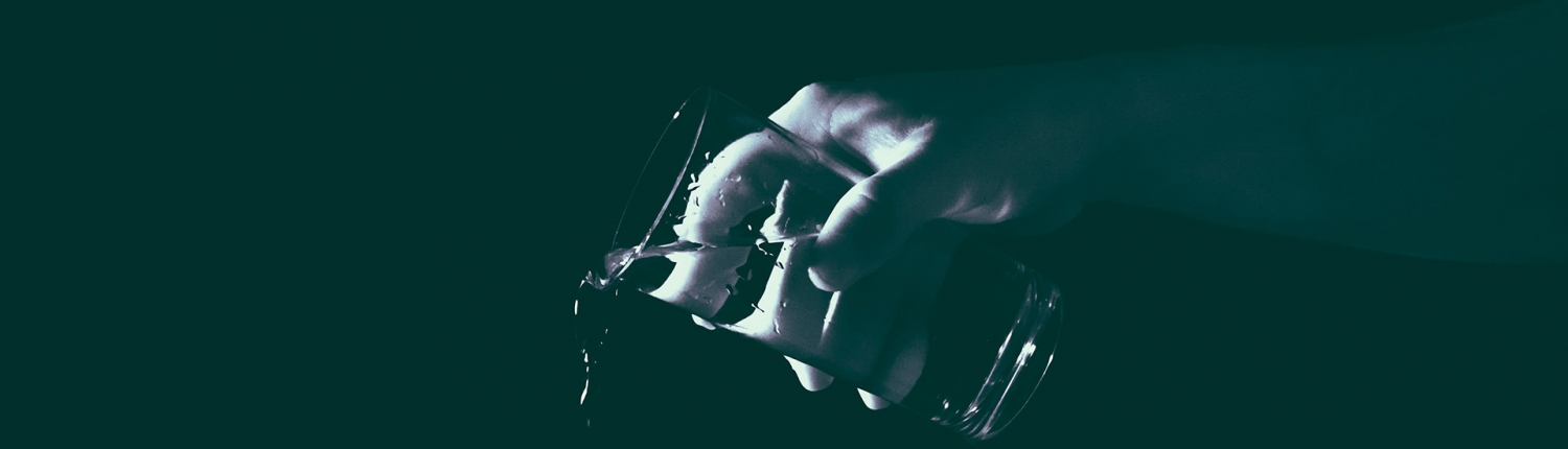 A black and while image of a hand pouring out a glass of water.