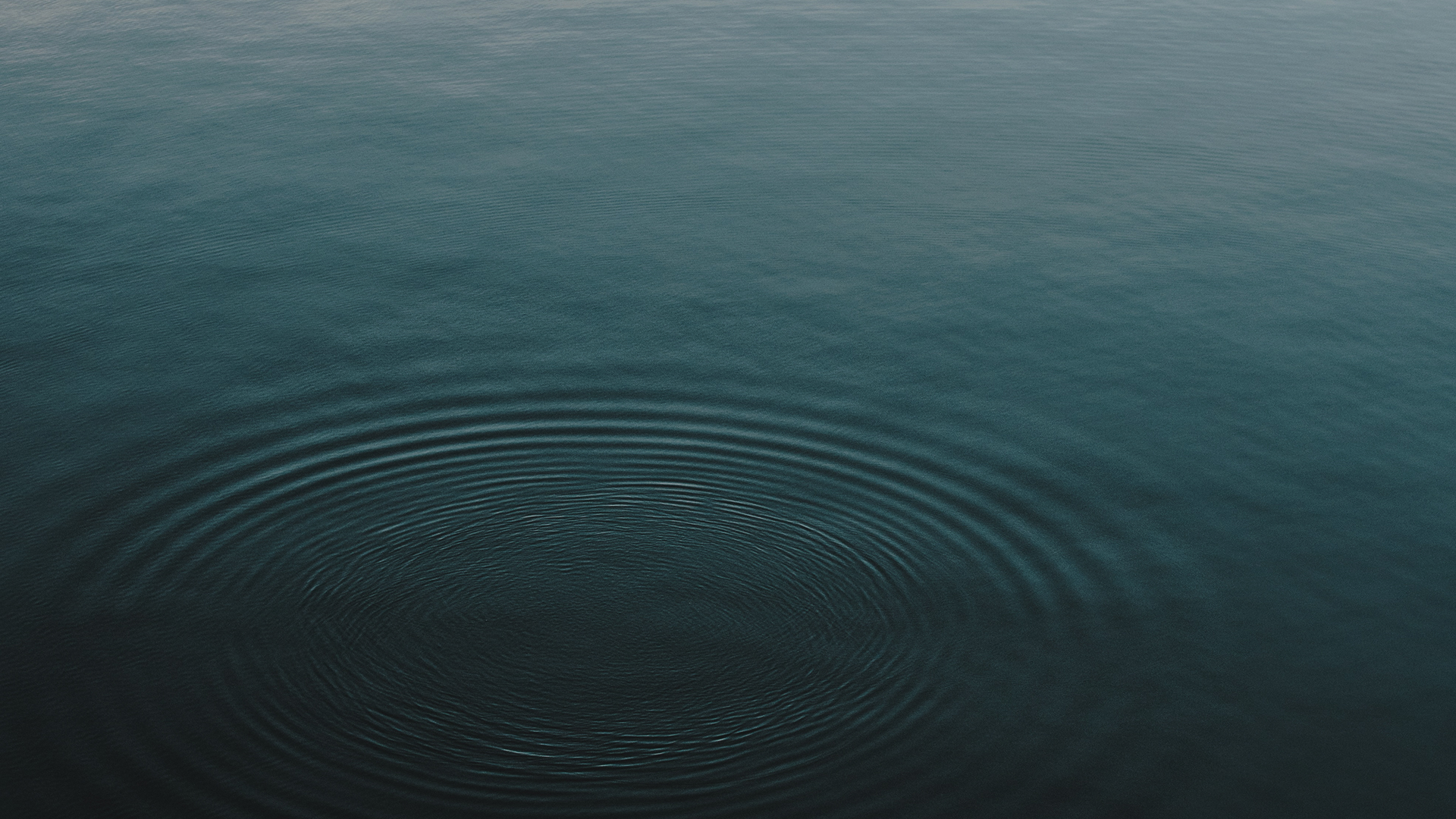 The surface of a dark blue lake with ripples in it.