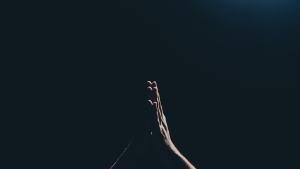 hands praying against a black background.