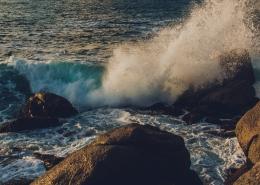 Waves crashing over large rocks.