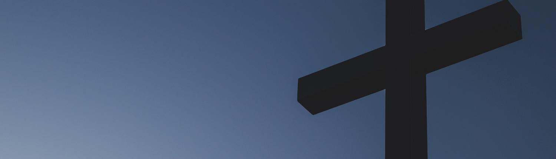 A wooden cross set against a blue sky.