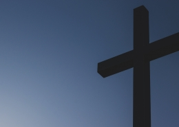 A wooden cross set against a blue sky.