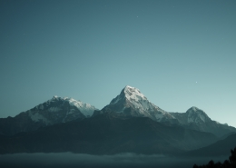 A dark blue sky with mountains.