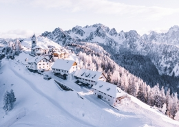 A snow covered mountain with cabins.