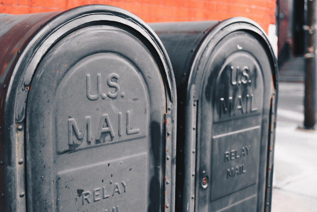 Two black mailboxes against an orange wall.