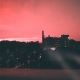 A pink skyline against a dark city.