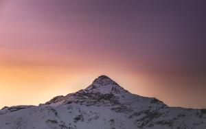 A snowy mountain peak against a sunset.