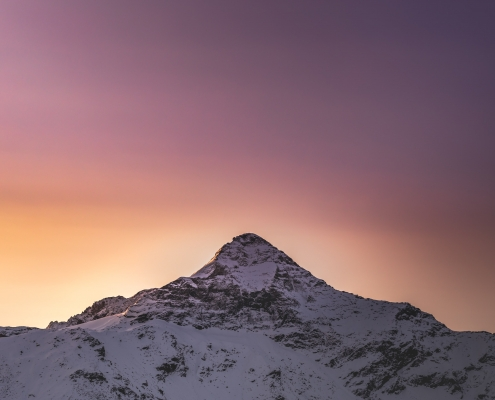 A snowy mountain peak against a sunset.