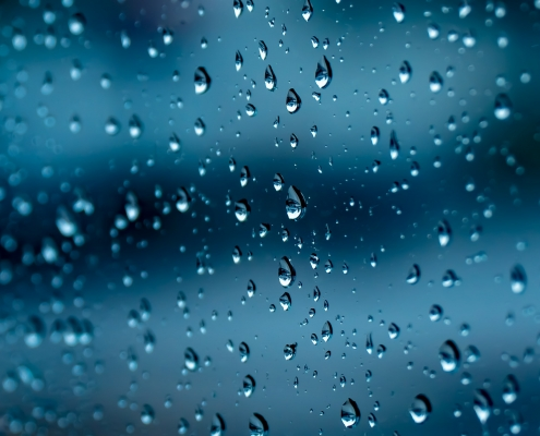 Rain on dark blue glass.