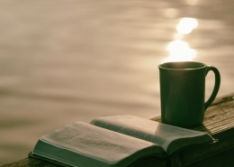 A mug and bible overlooking a sunset on a lake.