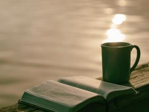 A mug and bible overlooking a sunset on a lake.