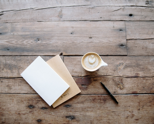 A cup of coffee, books, and a pen on a wooden table.