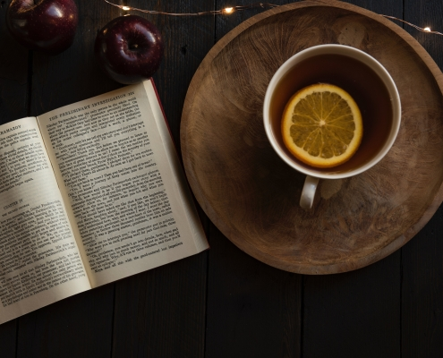 A book and a cup of tea with a slice of orange in it.