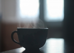 A mug sitting on a table with steam coming off it.