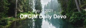 """A lake with pine trees on either side and the text, """"May 4, 2021. OPCM daily devo."""""""