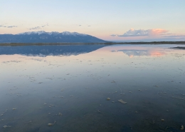 May 27th devo image, a lake at sunset with mountains in the background.