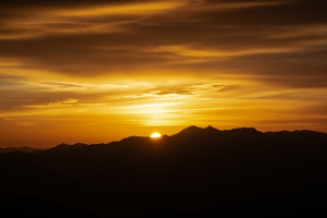 June 2nd devo image, a sunrise over mountains.