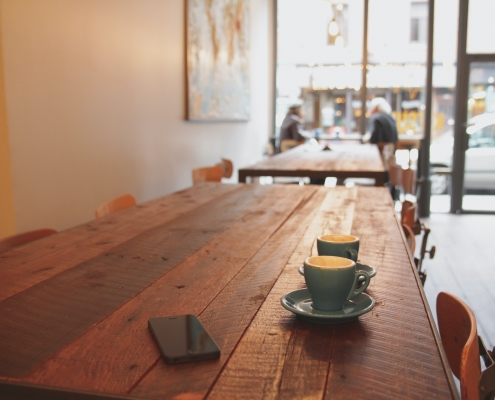 September devo image, two coffee cups on a wooden table.